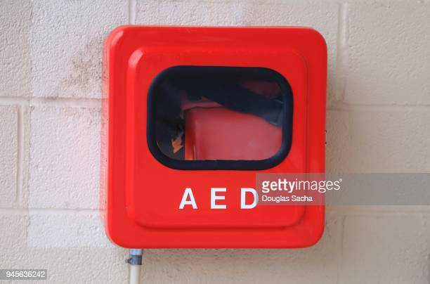 Automated External Defibrillator (AED) for heart attack emergency is mounted on a wall in a red box