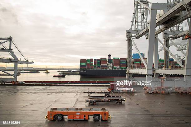 Automated guided vehicles stand beside gantry cranes on the dockside at the Delta Terminal operated by Europe Container Terminals BV at the Port of...