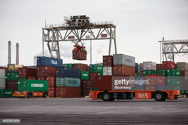 Automated guided vehicles transport shipping containers on the dockside as gantry cranes operate beyond at Europe Container Terminals BV Delta...