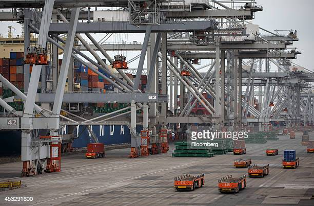 Automated guided vehicles transport shipping containers on the dockside as shiptoshore cranes operate at Europe Container Terminals BV Delta Terminal...