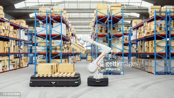 automated robot carriers and robotic arm in modern distribution warehouse - robot stock pictures, royalty-free photos & images