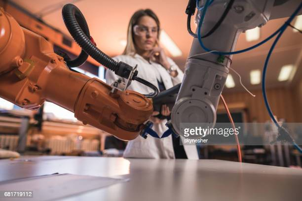 Automated robotic arms in laboratory with engineer in the background.