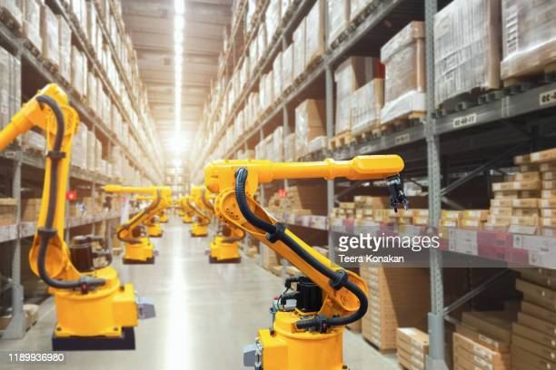 automatic robot mechanical arm is working in temporary storage - automated stock pictures, royalty-free photos & images
