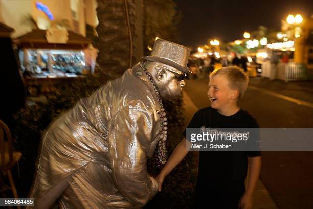 'Automatic' The Silver Robot entertains Evan Athey of Huntington Beach along Main Street Tuesday March 27 2007 in Huntington Beach Main Street is...