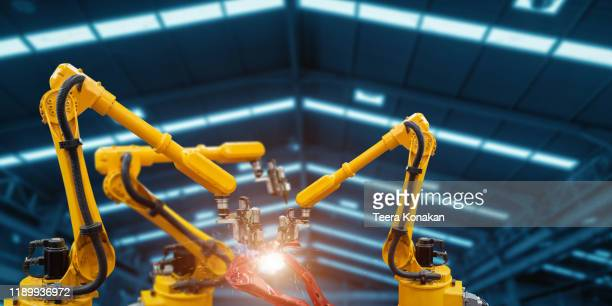 automatic welding robot mechanical arm is working in the modern automobile parts factory. - robotic arm stock pictures, royalty-free photos & images