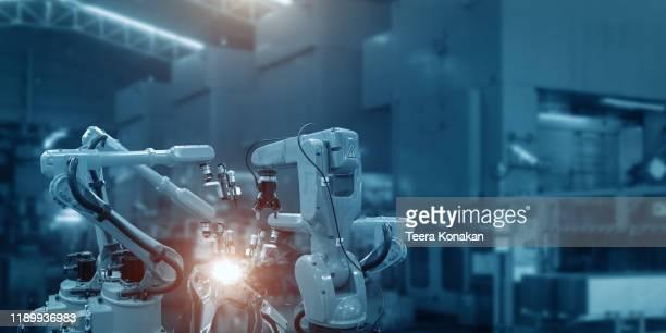 automatic welding robot mechanical arm is working in the modern automobile parts factory. - rechnerunterstützte fertigung stock-fotos und bilder