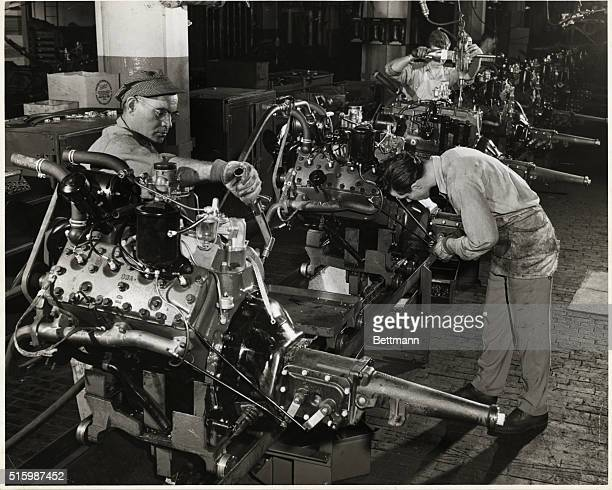 Automobile assembly workers dressup an engine just before placing it on the chassis at the Ford Motor Company's plant in River Rouge Michigan Undated...