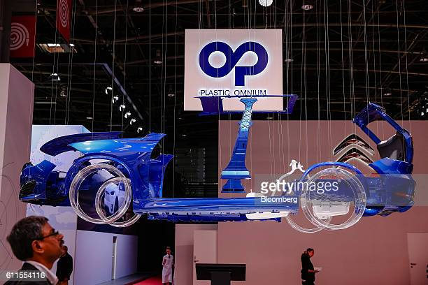Automobile body shell hangs above the Plastic Omnium SA exhibition stand on the second press day of the Paris Motor Show at Porte de Versailles...