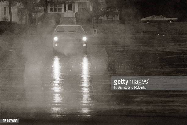 Automobile Car With Headlights On Coming Down Rainy Street At Night In Bad Weather Showing Rain Cars And Lights