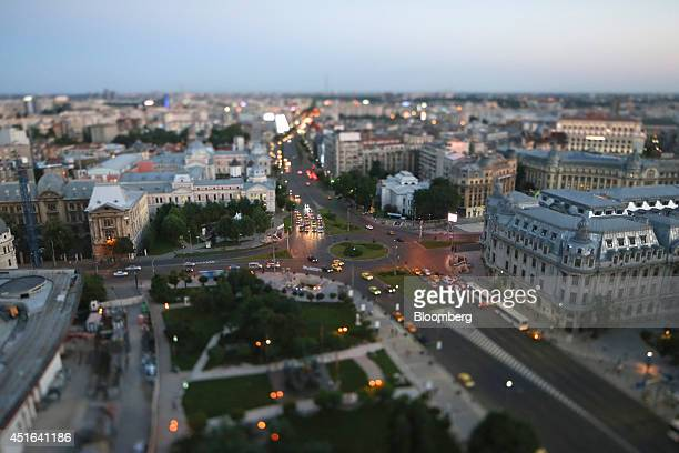 Automobile headlights illuminate a road in the early evening light as traffic moves towards the University roundabout in the center of Bucharest in...