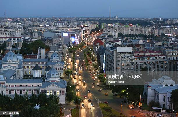 Automobile headlights illuminate a road in the late evening light as traffic moves towards the University roundabout in the center of Bucharest...