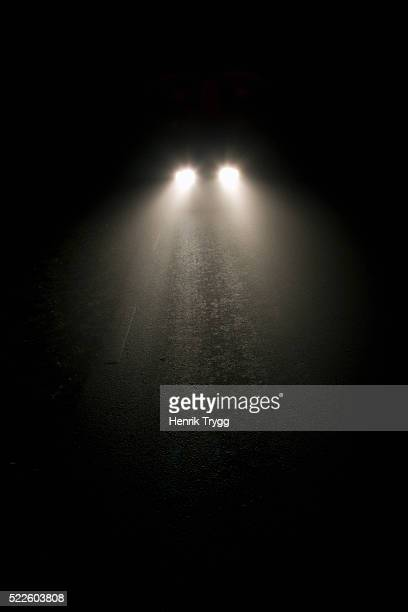 automobile lights on foggy night - headlight stock pictures, royalty-free photos & images