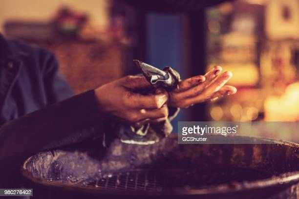automobile mechanic wiping her hands after an oil change - oil change stock pictures, royalty-free photos & images