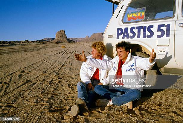 Automobile racing champion Jean-Pierre Jabouille and French singer Michel Sardou sitting by their car while participating together in the Paris-Dakar...