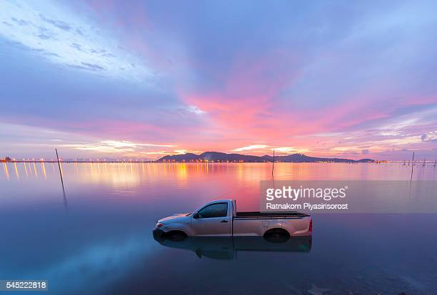 Automobile sinking in water in Sunset Scene