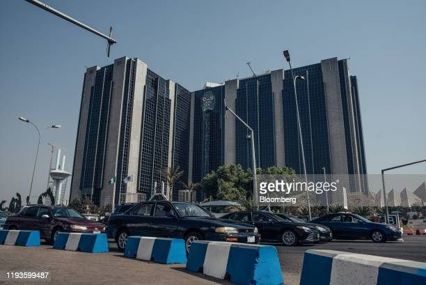 Automobiles drive past the headquarters of the Nigerian central bank in Abuja, Nigeria, on Friday, Jan. 10, 2020. Revenue in Nigeria has fallen short...