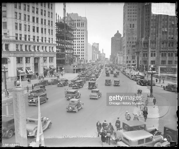 Automobiles driving and pedestrians walking on Michigan Avenue Wrigley building visible on the left Chicago Illinois 1929 From the Chicago Daily News...