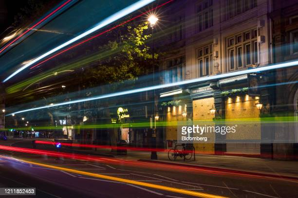 Automobiles leave light trails as they pass the boarded-up The Garrick Arms pub in central London, U.K. On Monday, May 4, 2020. Cabinet Office...