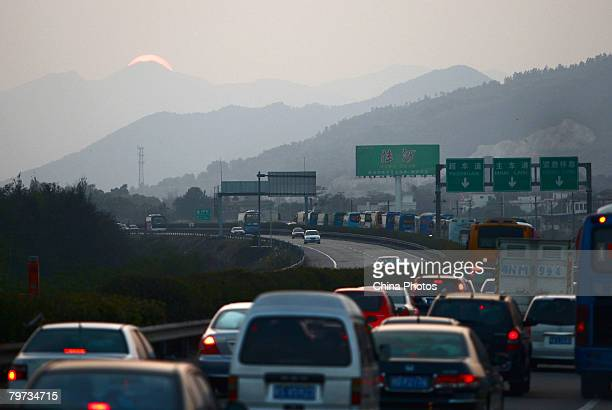 Automobiles move on the Houmen Section of Shenshan Highway at sunset on February 12, 2008 in Haifeng County of Guangdong Province, China. As the...