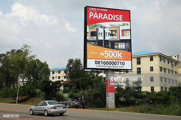 Automobiles pass a giant roadside advertisement advertising new residential homes for sale in Abuja Nigeria on Wednesday Oct 21 2015 A drop in crude...