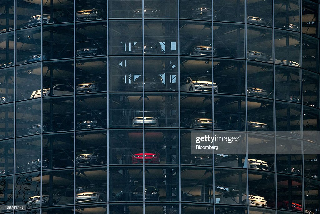 Automobiles, produced by Volkswagen AG (VW), sit behind windows inside the auto delivery tower at the VW headquarters in Wolfsburg, Germany, on Wednesday, Sept. 23, 2015. Volkswagen's escalating scandal over emissions-test cheating is beginning to ripple across the $10 trillion global corporate bond market. Photographer: Krisztian Bocsi/Bloomberg via Getty Images