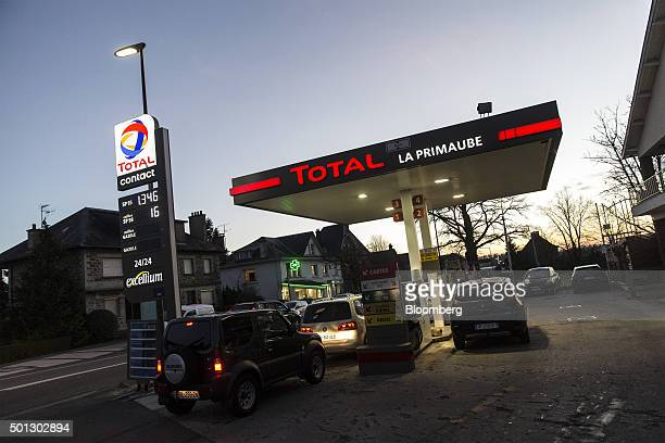 Automobiles sit at fuel pumps on the forecourt of a gas station operated by Total SA in LucLaPrimaube near Rodez France on Friday Dec 11 2015 Oil...