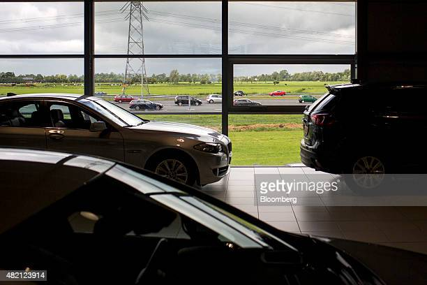 Automobiles sit inside a LeasePlan Corp used car leasing and contract hire showroom as traffic passes on a highway outside in Breukelen Netherlands...