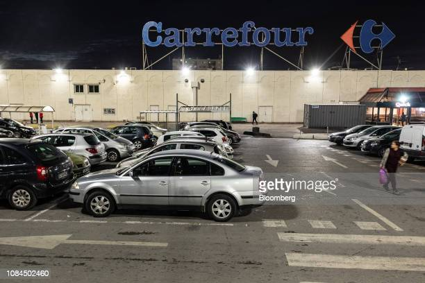 Automobiles sit parked outside a Carrefour SA hypermarket store at night in Marseille France on Thursday Jan 17 2019Shares in French retailers...