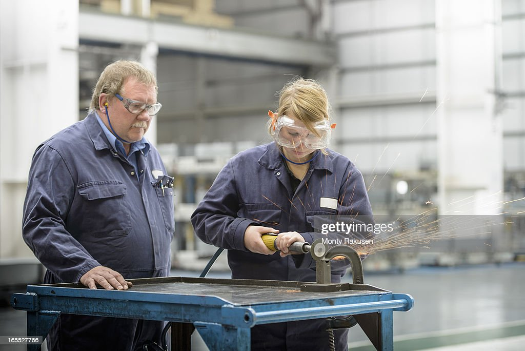 Automotive apprentice and tutor using machinery, wearing boiler suits and protective goggles in car plant : Stock Photo
