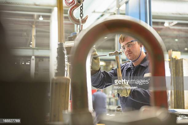 Automotive apprentice wearing boiler suit and protective goggles in car plant