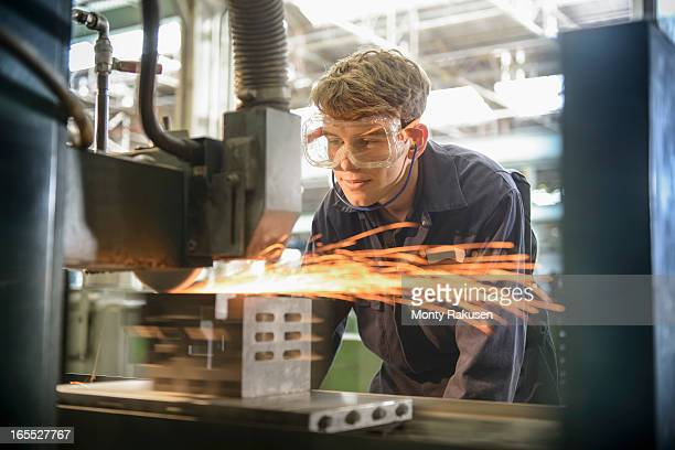 Automotive apprentice wearing boiler suit and protective goggles using grinding machine in car plant
