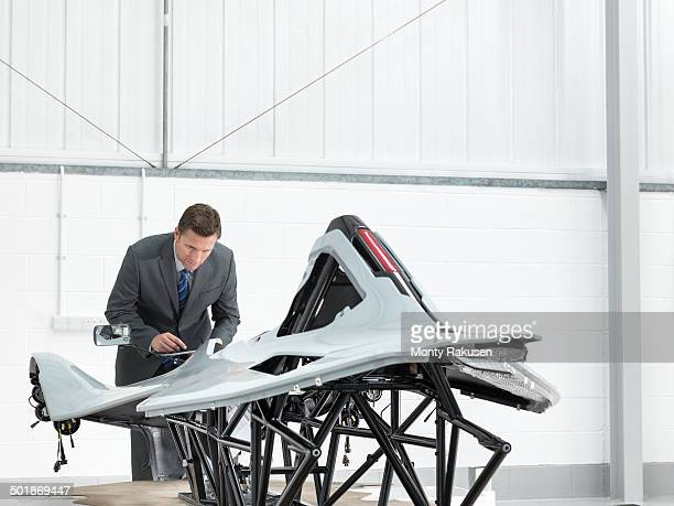 Automotive designer inspecting part-built supercar in car factory