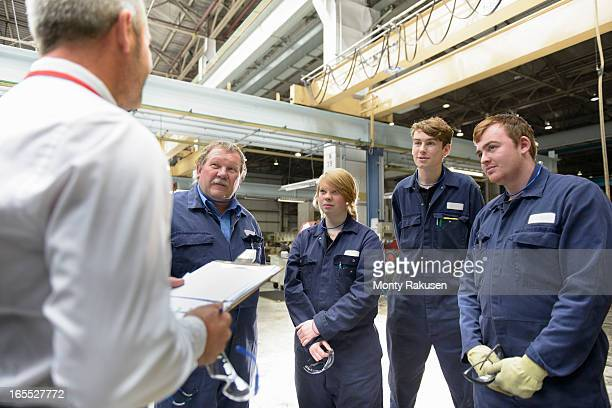 Automotive engineers wearing boiler suits and manager discussing project in car plant