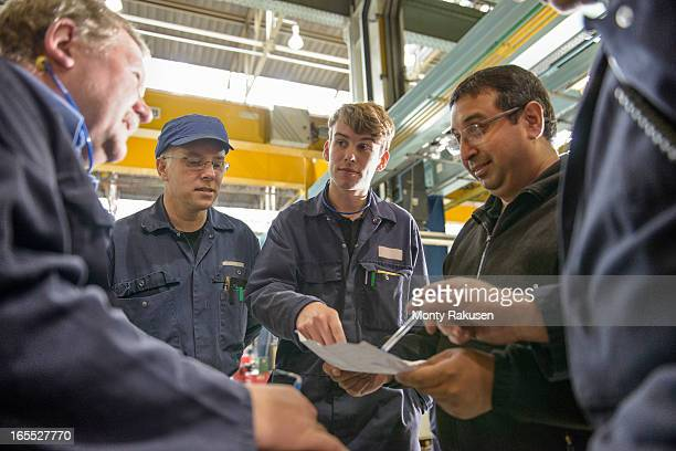 Automotive engineers wearing boiler suits discussing project in car plant