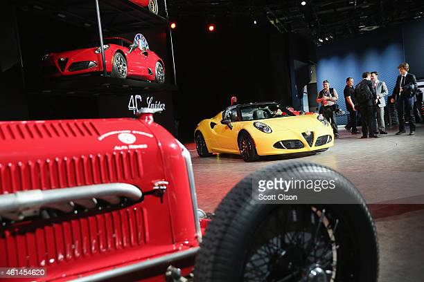 Automotive journalists look over the new Alfa Romeo 4C convertible at the North American International Auto Show on January 12 2015 in Detroit...