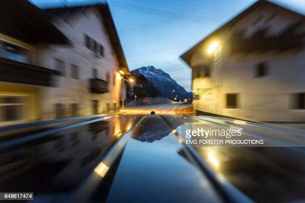 automotive on board a car long exposure rigging shot from the top of a black german van, streaking reflections in the roofs surface of the car in foreground, antenna and front end of the roof in mid ground, the background is blurred motion. - ems forster productions stock pictures, royalty-free photos & images