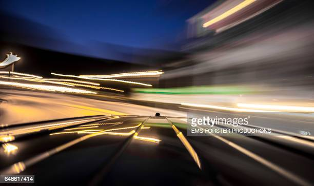 automotive on board a car long exposure rigging shot of the top of a black german van, streaking reflections in the roofs surface of the car in foreground, antenna and front end of the roof in mid ground, the background is blurred motion. - ems forster productions stock pictures, royalty-free photos & images