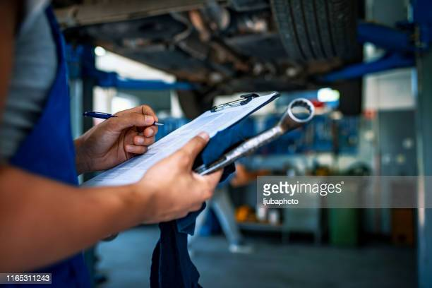 automotive specialist adjusting an engine - garage stock pictures, royalty-free photos & images