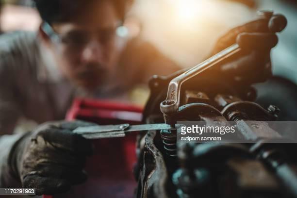 automotive technicians. setting the valve for the car in the garage. - maschinenteil hergestellter gegenstand stock-fotos und bilder