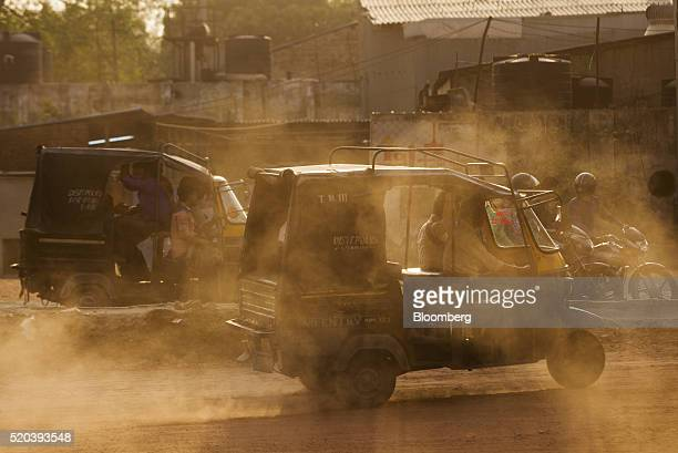 Autorickshaws kick up dust as they travel near the Delhi city boundary in Faridabad Haryana India on Friday April 8 2106 The oddeven car rationing...