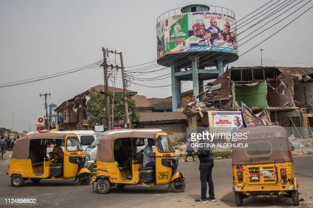 Autorickshaws pass under a billboard of Atiku Abubakar the official opposition candidate in the upcoming elections posted at a crossroad in Aba one...