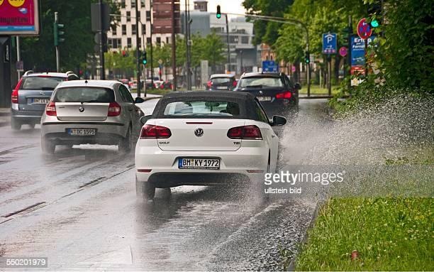 Autos im Regen, durch stehendes Wasser am Straßenrand erhöhte Aquaplaninggefahr
