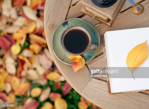 Autumn, a cup of coffee,  yellow leaf on book on table