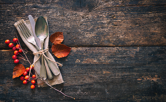 Autumn background with vintage place setting on old wooden table 1057528864
