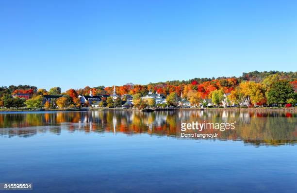 autumn foliage reflection along the shores of lake winnipesaukee - new hampshire stock pictures, royalty-free photos & images