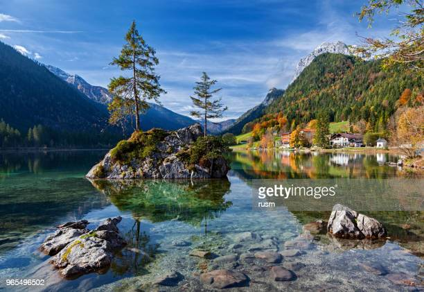 Autumn forest reflected in calm lake. Hintersee lake in Berchtesgaden park, Germany.