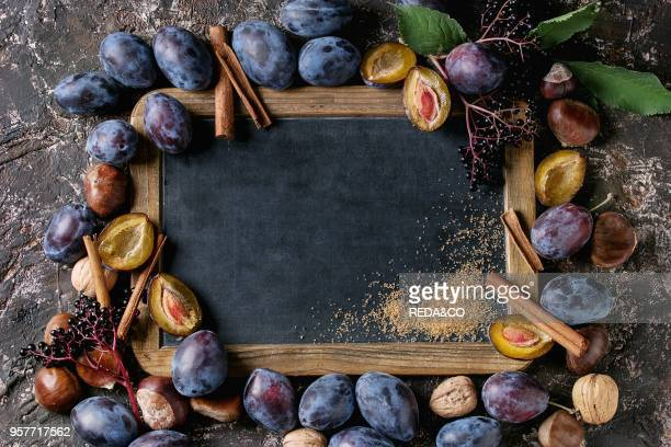Autumn frame from plums nuts cinnamon and brown sugar with empty vintage chalkboard over brown concrete background Top view with space for text Fall...