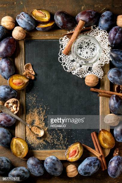 Autumn frame from plums nuts cinnamon glass jar and brown sugar with empty vintage chalkboard over brown concrete background Top view with space for...