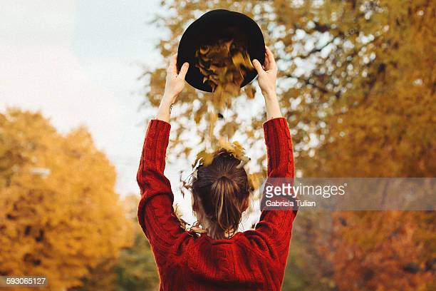 Autumn leaves falling from girl's hat