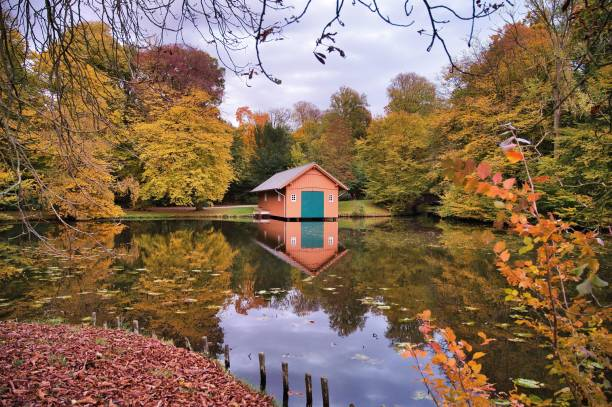 Autumn, leaves, lake with reflection and hut, boathouse MARIE, Buergerpark, Bremen, Germany